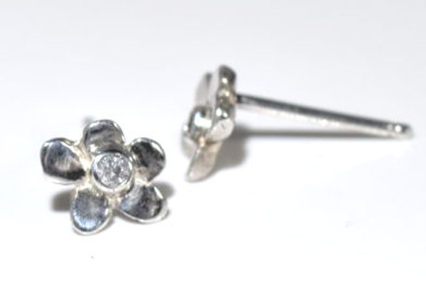 The silver diamond flower studs are hand crafted in Portland, Maine.  The studs have a 1.8 mm. round brilliant cut diamond set in a bezel in the center of the flower.  The flower measures 7.5 mm x 6.5 mm. and weighs 1.29 grams.  The earrings have a polished finish.