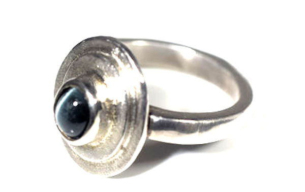 The Maine cats eye tourmaline ring is hand crafted in Portland, Maine.  The cats eye blue green tourmaline is from Newry, Maine.  The cats eye is a 6 mm x 5 mm roval shape.  The stone is set in a sterling silver double step style ring.  The ring is a size 6.75 and can be sized upon request.  The ring weighs 6.7 grams and measures 16 mm. x 15 mm. on the outer step section of the top of the ring. The ring is solid.