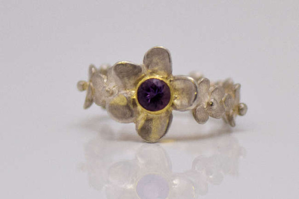 The amethyst flower ring is hand crafted in sterling silver in Portland, Maine.  The top has a flower measuring 14 mm. x 13.5 mm. with a 4 mm. round faceted medium bright colored amethyst set in an 18 k yellow gold bezel.  The shank is a 8 multi flower band and at the widest it is 6.5 mm.  The shank is also sterling silver.  This ring weighs 5.5 grams and is solid and is a size 6.75.