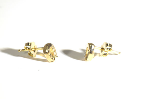 The tiny gold horse shoe studs are  hand crafted in Portland, Maine.  The horse shoe was carved and cast measuring 1/4 x 1/4 x 1/16 inch and weigh 1.7 grams.  The studs have a polished finish and are solid.The earrings  3/8 x 5/16  x 3/8 inch. The earrings are 14 K yellow gold.