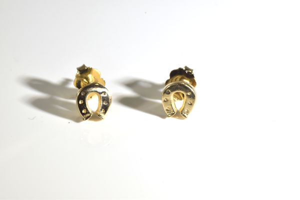 The small gold horse shoe stud earrings are hand crafted in Portland, Maine.  The horse shoe has a polished finish, are solid,  and weighs 2.2 grams.  The earrings  3/8 x 5/16  x 3/8 inch.  The earrings  3/8 x 5/16  x 3/8 inch. The earrings are 14 K yellow gold.