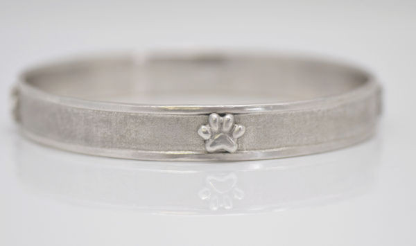 The sterling silver paw print bangle is hand crafted in Portland, Maine.  The bangle fits an average 7 inch wrist.  The width of the bracelet is 10 mm. x 2 mm.  and has a raised polished 2 mm. edge and a brushed recessed center section.  There are four 9 mm. x 7 mm. sterling silver  two dimensional paws on it.  The bracelet weighs 32.3 grams and is solid.  A portion of the profits will be donated to the Animal Refuge League locate in Westbrook, Maine.
