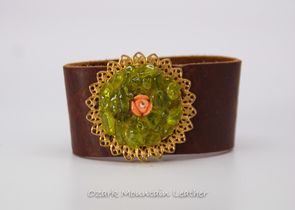 Green vintage brooch on brown leather cuff