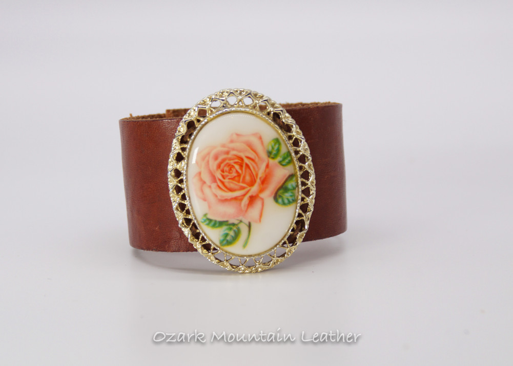 Pink floral brooch on brown leather cuff