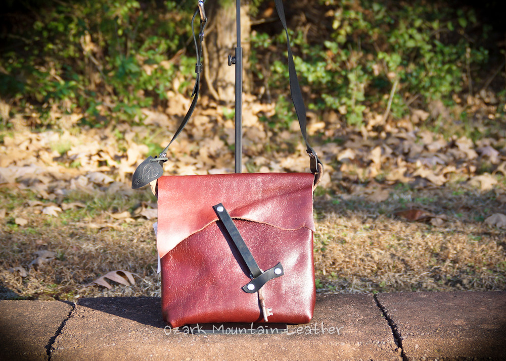 Burgandy leather cross body bag with black straps made by Ozark Mountain Leather.  With skeleton key closure.