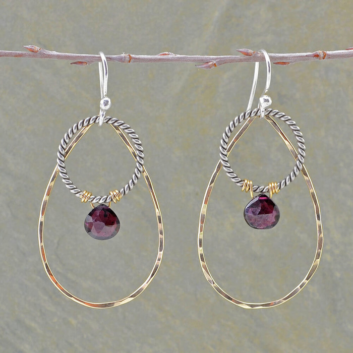 unique handmade earrings with one sterling silver hoop overlapped with oval hoop filled with 14kt and garnet stones: view 1