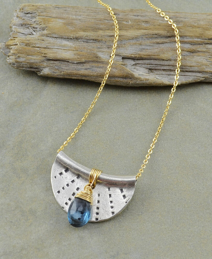 Handcrafted crescent moon necklace made with stamped sterling silver and a blue topaz gemstone: view 1