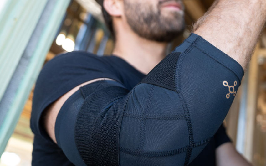 A man wearing the Adjustable Support Elbow Sleeve.