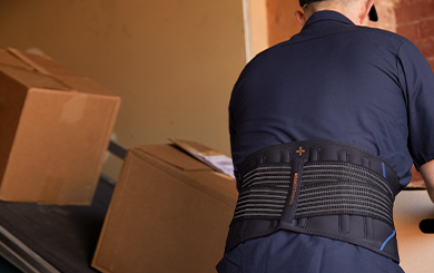 A man lifting boxes wearing the Adjustable Back Brace.
