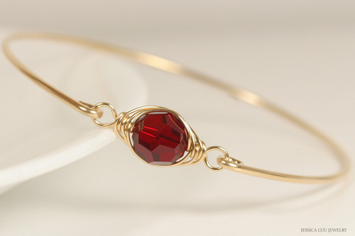 14k yellow gold filled wire wrapped bangle bracelet with garnet red siam crystal handmade by Jessica Luu Jewelry