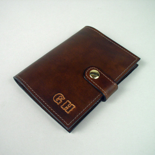 Leather passport holder credit card wallet personalized with undyed embossed initials.