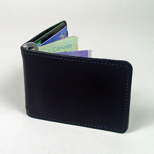 Black leather money clip wallet with goatskin interior pockets.