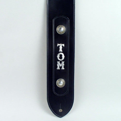 Metal silver letters centered between metal conchos on this personalized guitar strap.