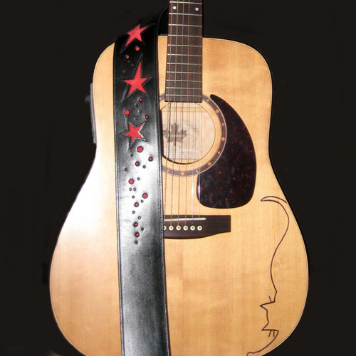 Custom cowhide guitar strap decorated with red leather inlays in a star pattern.