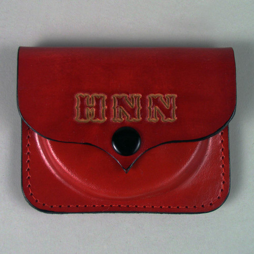 Red leather personalized change purse with undyed letters.