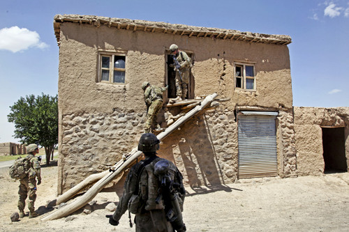 U.S soldiers evacuating a worn stucco house