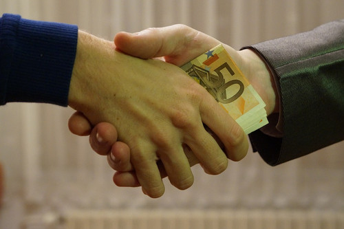 handshake partially concealing the exchange of money