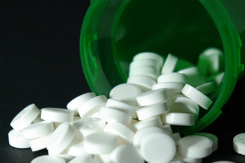 green pill bottle toppled over, pills spilling out