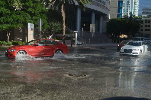 cars pass through a partially flooded street