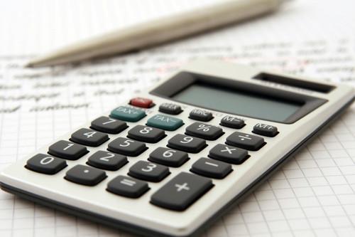 calculator atop notebook with pen