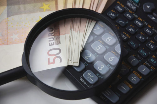 euros and calculator magnified by magnifying glass