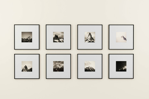 gallery wall of framed artwork depicting mountain ranges