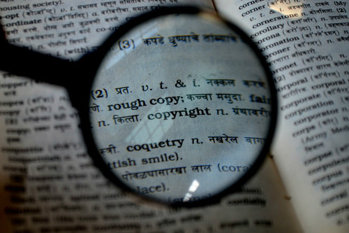 magnifying glass magnifies the word copyright in a dictionary