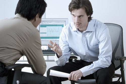 businessmen discuss performance graphs