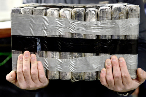 man holding nondescript bundles attached with duct tape