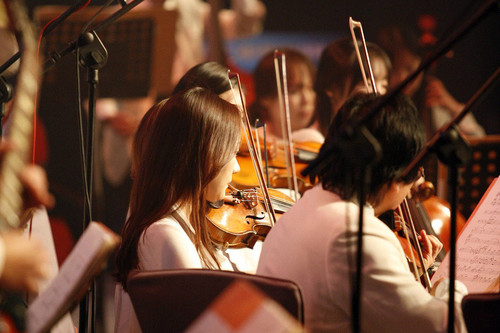 woman playing violin in an orchestra