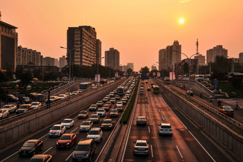 cars on the highway in Beijing, China during a sunset