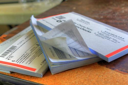 messy pile of 3 checkbooks