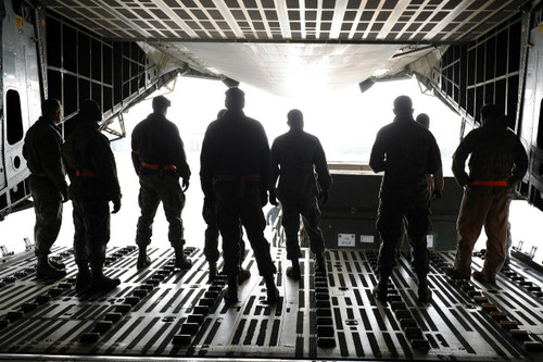 military men standing in a transport vehicle