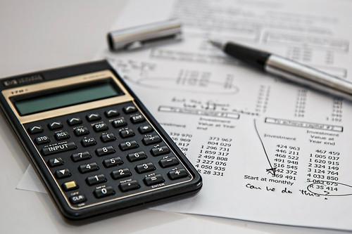 calculator, expense sheet, and pen on a desk