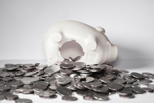 coins spilling out of a white piggy bank