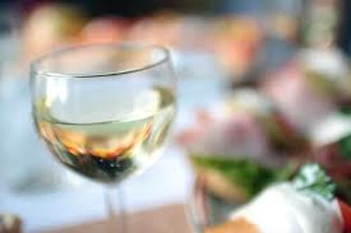 glass of white wine among a blurred backdrop
