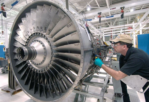 Man intently works on repairing airplane engine, industrial setting