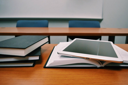 books, tablet, stacked on university classroom table
