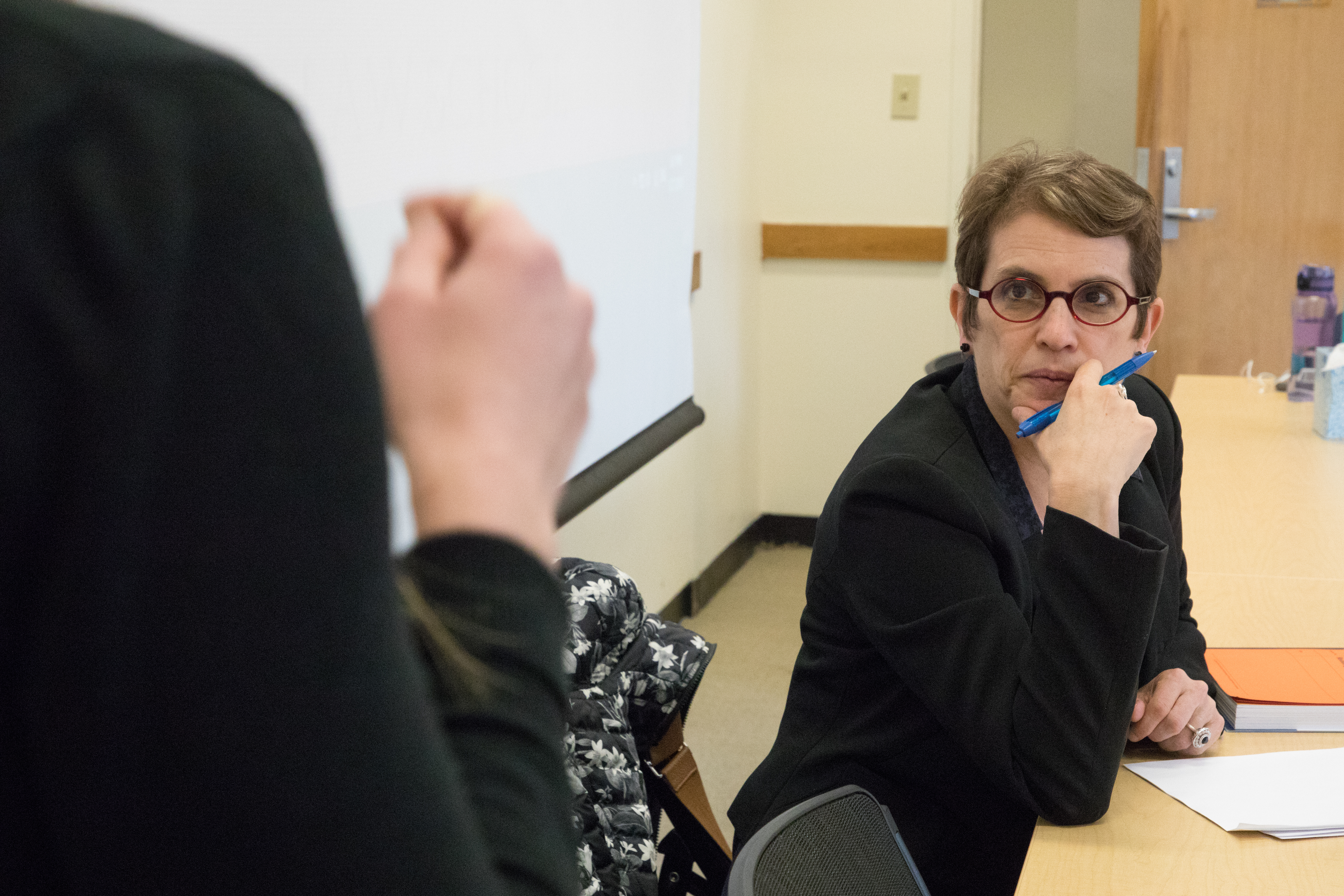 Professor Sharon Block listening to a student at her desk