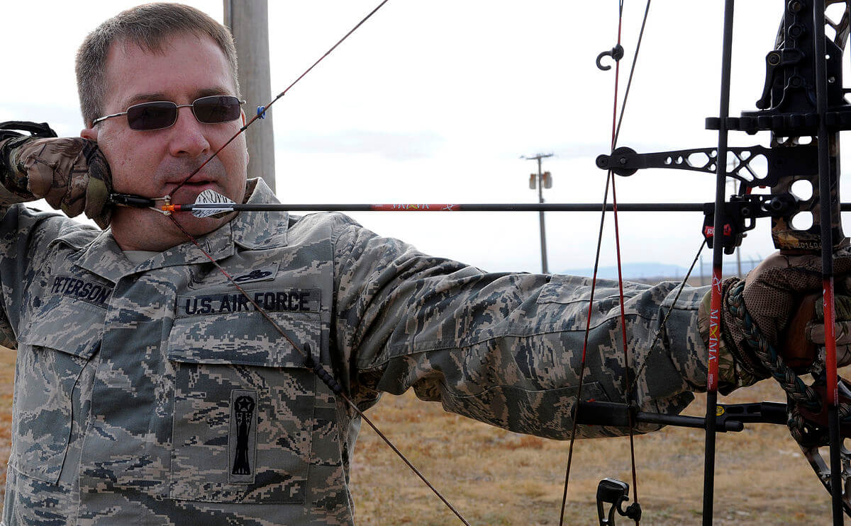 airforce man holding bow hunting equipment