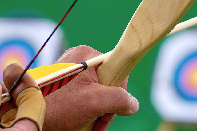 close up of hand knocking arrow on bow