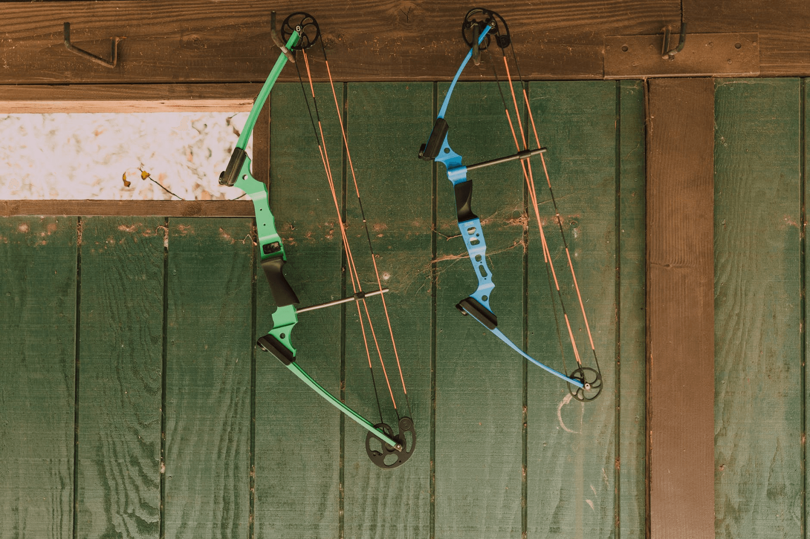 A green and a blue archery bow
