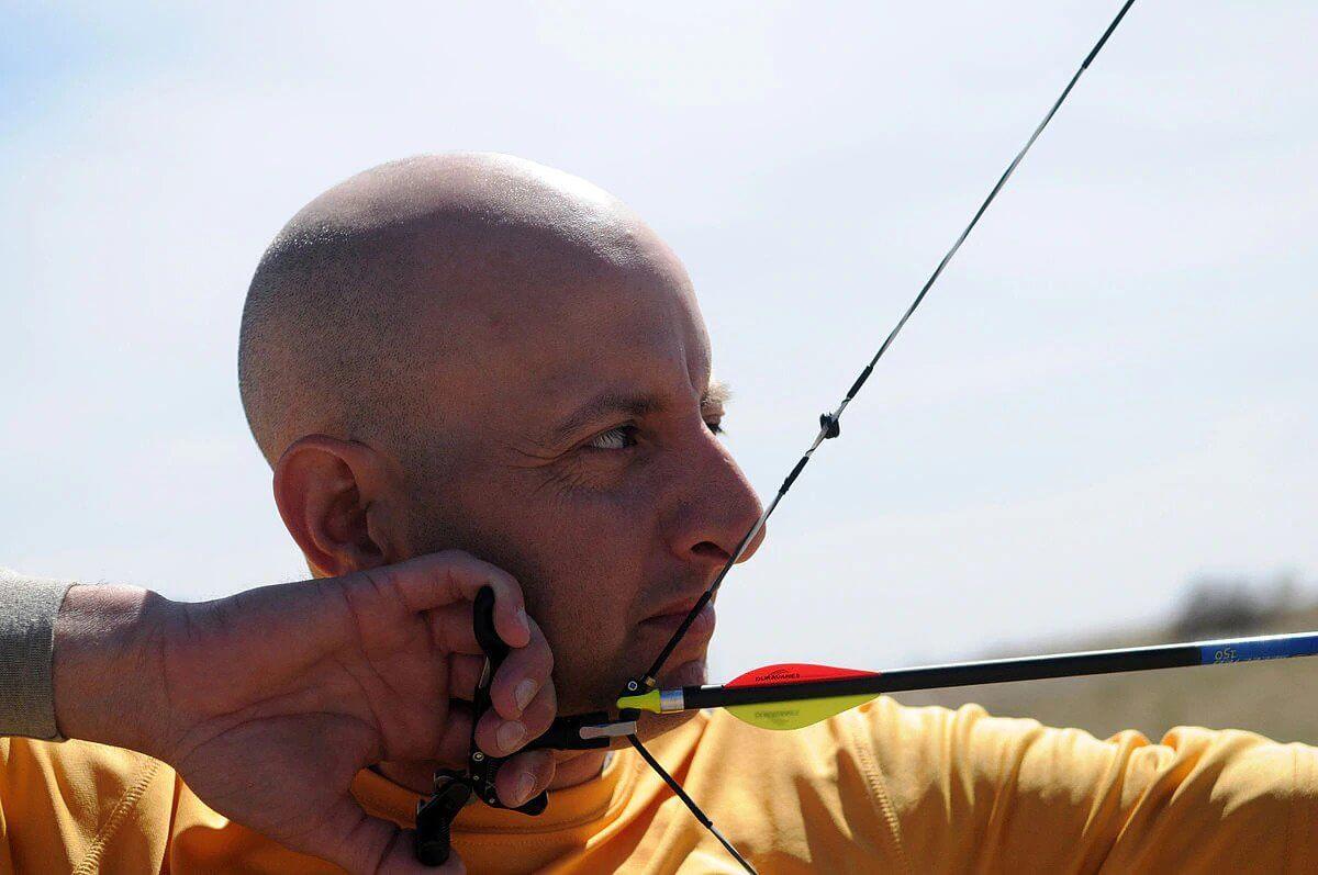 man aiming a bow and arrow