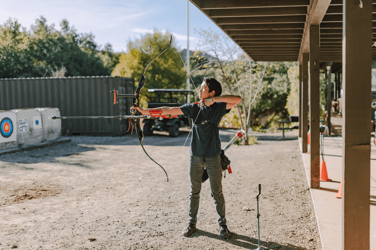 Man aiming a recurve bow with a stabilizer