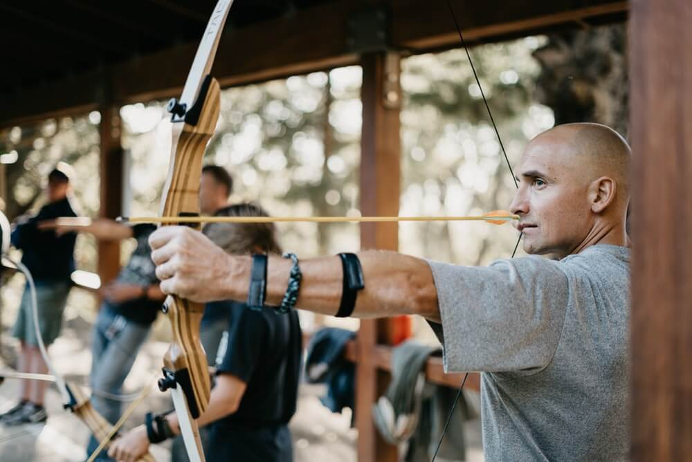 man shooting a recurve bow