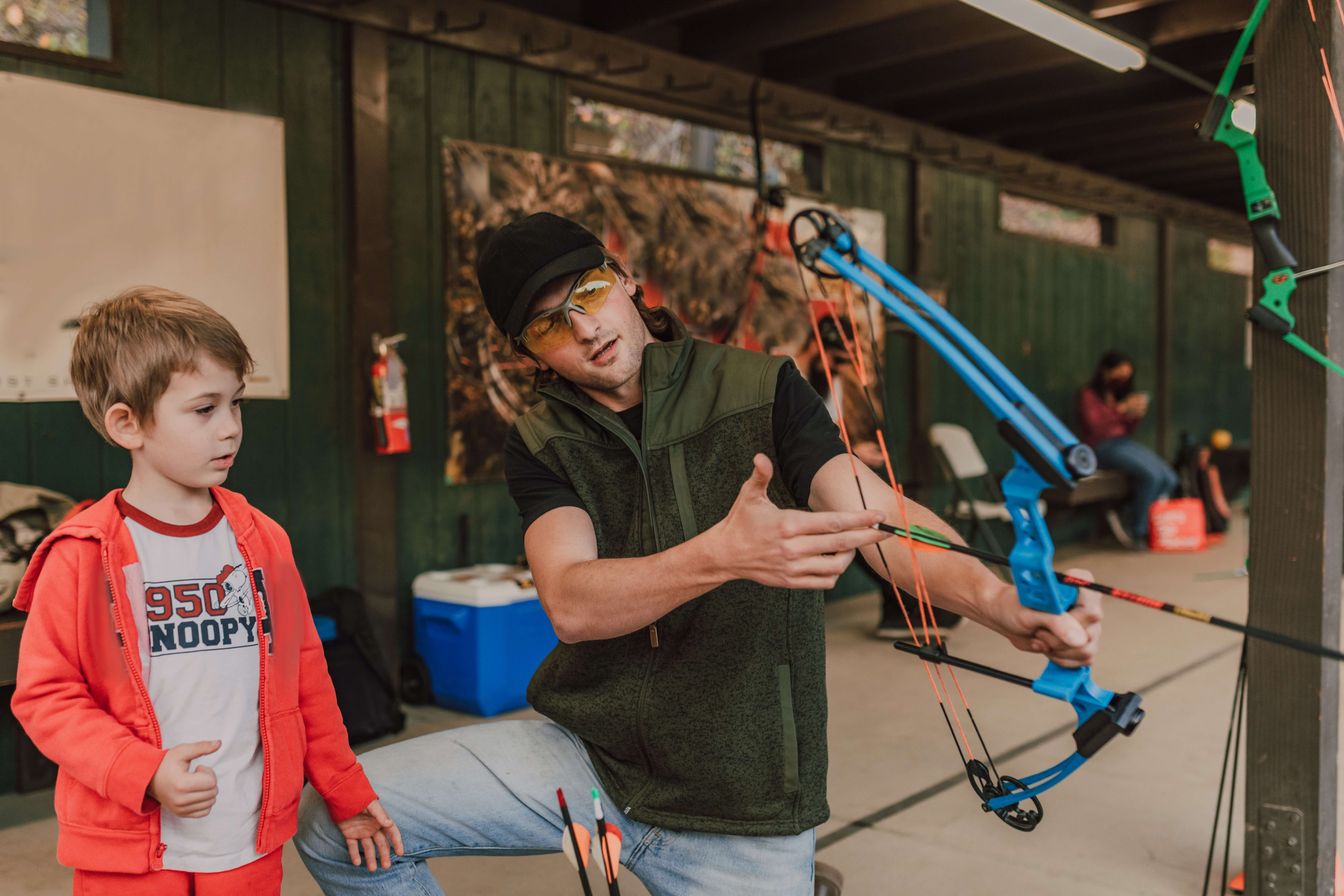 man showing a boy how to use a compound bow