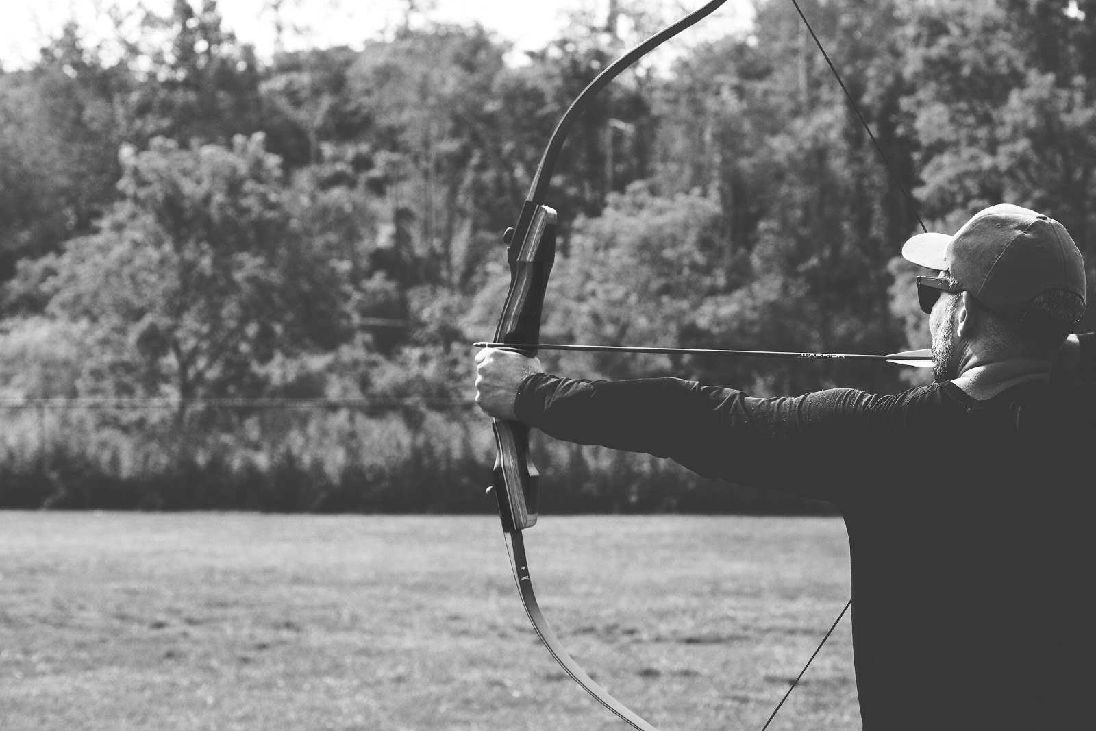 man shooting recurve bow black and white