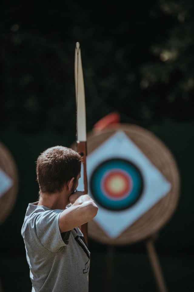 rear shot of man aiming bow at target