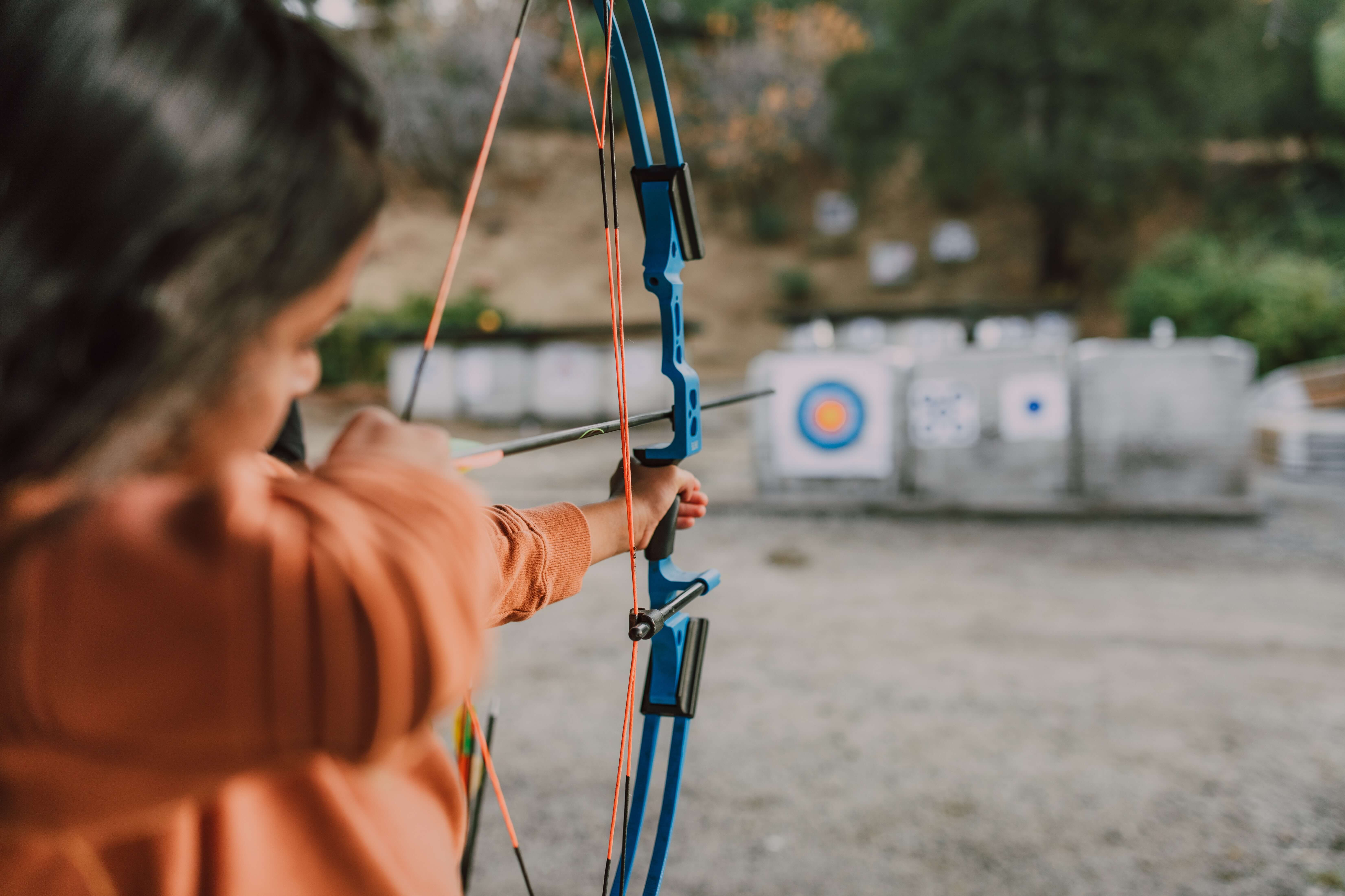 selective focus of young girl aiming compound bow at outdoor target
