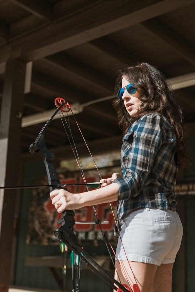 Woman standing outside with a compound bow
